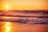 Sunrise and shining waves in ocean — Стоковое фото