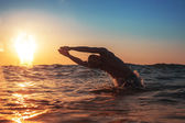 Young man swiming in the sea over yellow sunrise  — Stock Photo