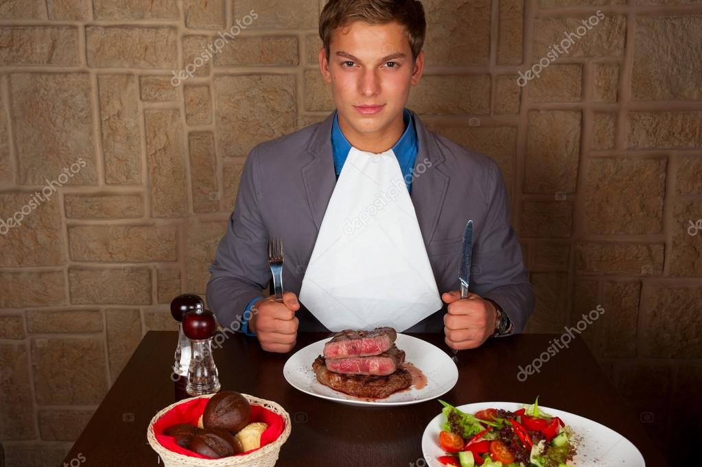 Man holding a knife and a fork ready to eat a beef steak  Stock Photo #19800107