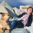 Stock Photo: Man relaxing with his dog at the beach
