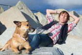 Man relaxing with his dog at the beach — ストック写真