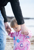 Baby girl holding her father's hands — Stock Photo
