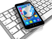 Smartphone auf computer-tastatur und welt-globus — Photo