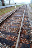 Railroad tracks headed towards small town — Stockfoto