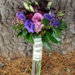 Wedding bouquet against a tree — Stock Photo