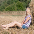 Girl sitting on hay - Stock Photo