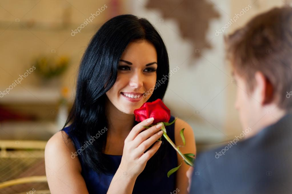 Young happy couple romantic date at restaurant, celebrating valentine day man give red rose to his girl — Stock Photo #16260237