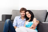 Couple sitting on floor near couch — Stock Photo