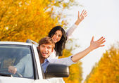 Young happy couple driving in car — Stock Photo
