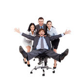 Excited Business people push colleague sitting in chair — Stock Photo