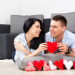 Young love couple holding lot of red valentine's hearts together — Stock Photo