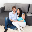 Young couple sitting on floor near sofa — Stock Photo #31732773