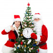 图库照片: Santa Claus and christmas girl hold clock