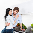 Couple using laptop at their kitchen home happy smile cooking — Stock Photo