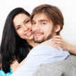 Young couple sitting on floor near sofa — Stock Photo #31734955