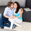 Young couple sitting on floor near sofa — Stok fotoğraf