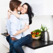 Stock Photo: Couple kissing at their kitchen