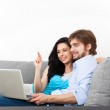 Young couple sitting on a sofa using laptop — Stock Photo