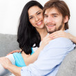 Young couple sitting on the sofa — Foto de Stock