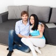 Young couple sitting on floor near sofa — Stockfoto