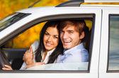 Mladí úsměv pár jedoucím autě — Stock fotografie