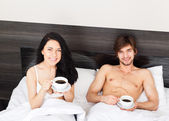 Young couple drink coffee in bed — Stock Photo
