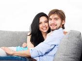 Jovem casal sentado no sofá — Fotografia Stock