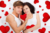 Love valentine day couple holding red heart together lying in a bed — Stock Photo