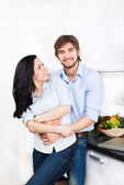 Happy couple cooking at their kitchen — Stock Photo