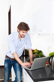 Young man at kitchen home happy smile using laptop cooking — Stock Photo