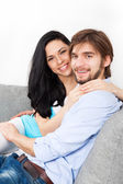 Young couple sitting on the sofa — Stok fotoğraf