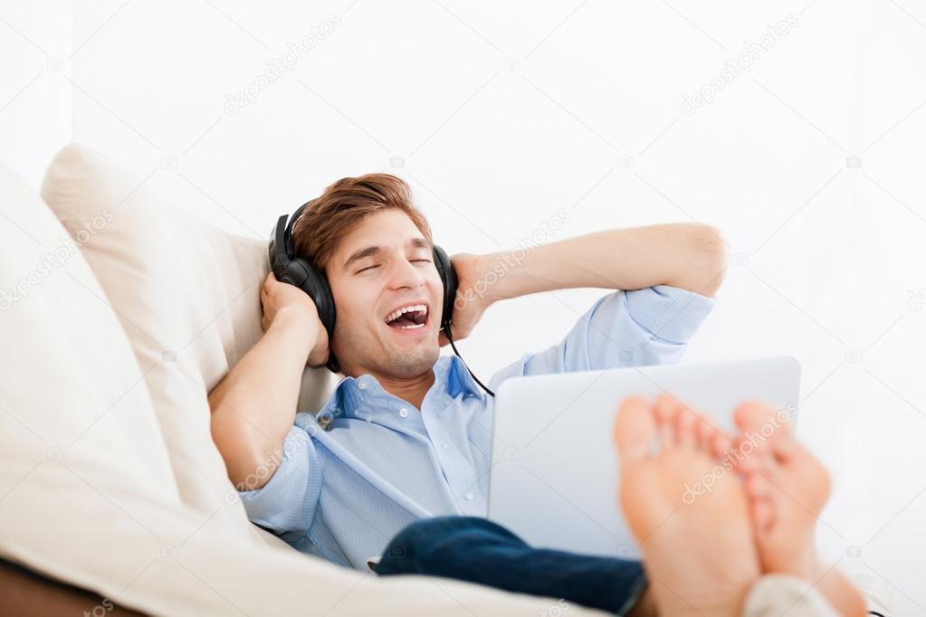 Man listening music in headphone on the sofa at home for Listen to house music