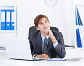 Business man look up sitting at office desk — Stock Photo
