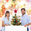Christmas holiday happy couple hold white board — Stock Photo