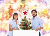 Christmas holiday happy couple hold white board — Zdjęcie stockowe