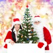 Santa Claus and christmas girl near tree hold white board  — Stock Photo