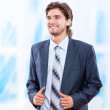 Young business man smile in bright blue office — Stock Photo