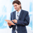 Business man using tablet pad computer in bright blue office, touch screen young businessman — Stock Photo