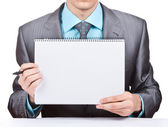 Businessman holding blank notepad — Stock Photo