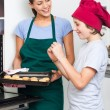 Mother and son taking cookies from oven — Stock Photo #43554605