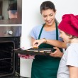 Mother and son taking cookies from oven — Stock Photo #43554611