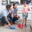 Father, mother and daughter sweeping floor — Stock Photo #43554619