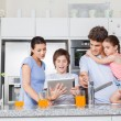 Family using a tablet pc in kitchen — Stock Photo #43555291