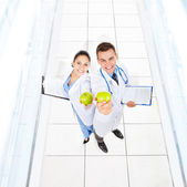 Doctors hold green fresh apples — Stock Photo
