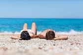Couple lying on beach — Stock Photo