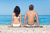 坐在海滩上的情侣 — 图库照片