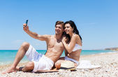 Couple taking self photo on beach — Stockfoto