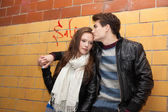 Couple In Winter Jackets Leaning On Tiled Wall — Stock Photo