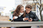 Couple Using Cell Phone While Leaning On Bench — Stock Photo
