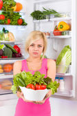 Unhappy woman holds salad — Stock Photo
